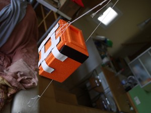 An orange polystyrene box with a lot of tape and wires